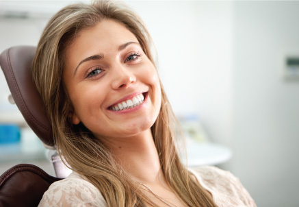 A woman smiling in the dental chair after her ZOOM! one-visit whitening