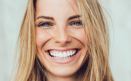 A young woman with porcelain veneers flashing a big grin