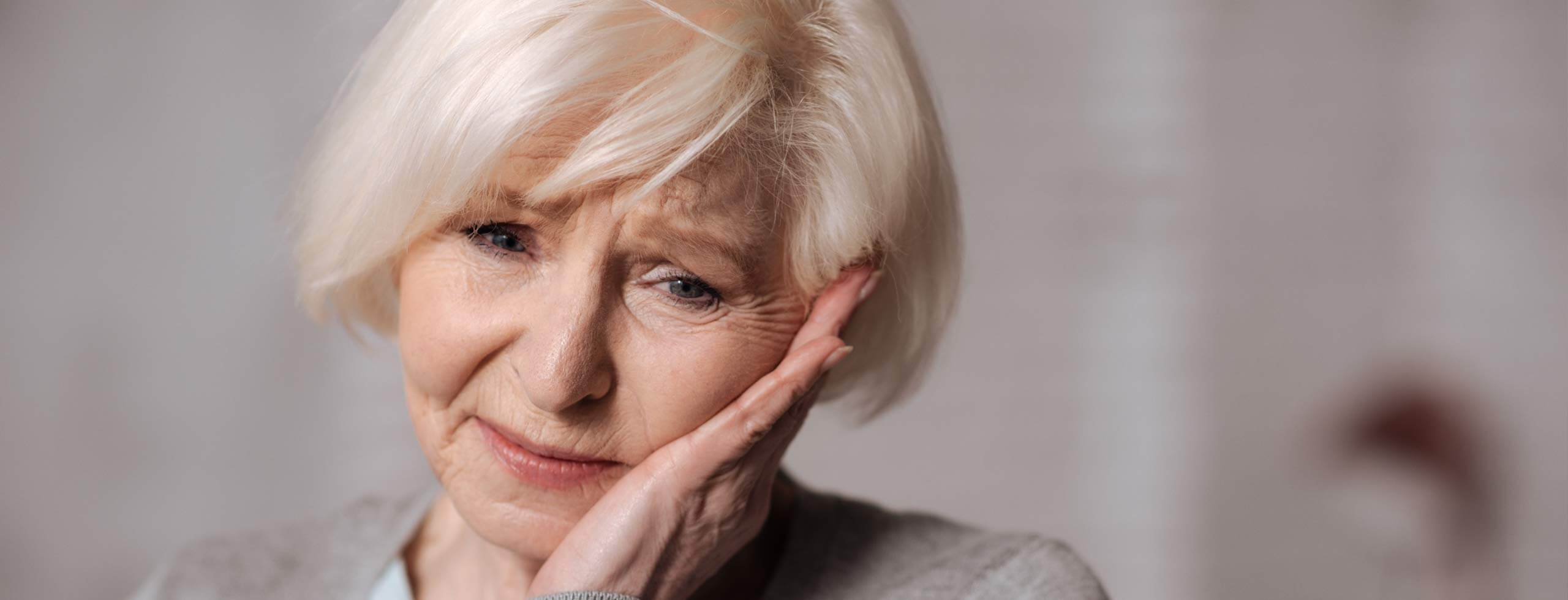 Older woman frowning and holding the side of her face because of TMJ pain.