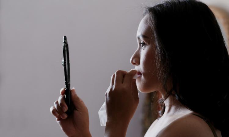 Brunette woman examines her skin health in a handheld mirror