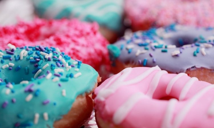 Closeup of donuts with pink, white, blue, and purple icing and sprinkles that contain sugar that can harm teeth