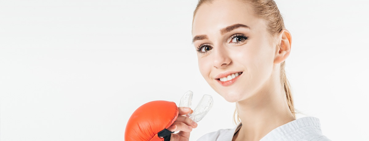 a teenage girl smiling as she puts in her custom mouthguard before her boxing match