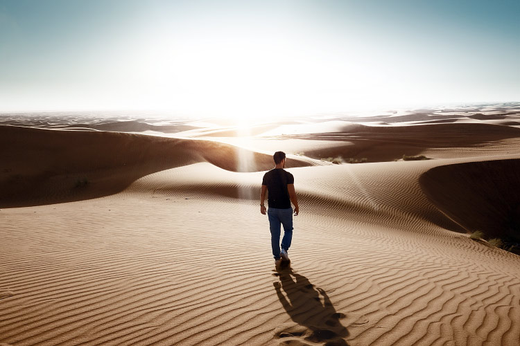 Lone man walking in a desert with sand ripples and a clear sky, representative of his dry mouth symptoms