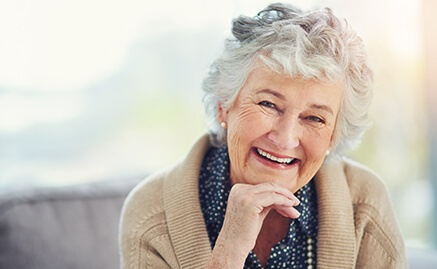 An elderly woman with dentures smiling with her chin resting on her hand