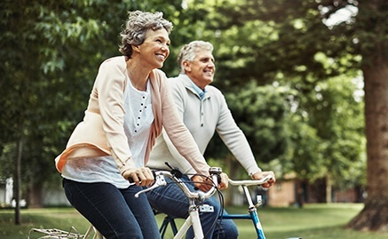 An older couple riding bikes in a park
