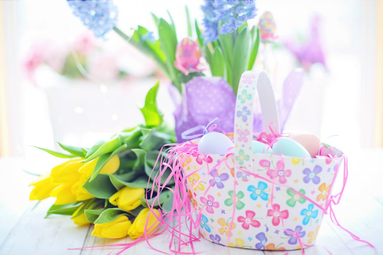 Floral Easter basket with Easter eggs next to a bouquet of yellow tulips