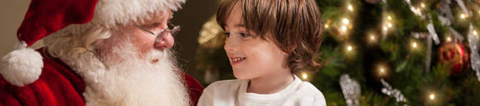 Young kid sitting on Santa's lap for Christmas