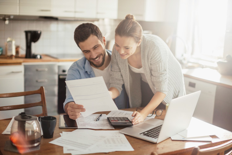 A husband and wife smile while looking over the finances because they save money using the Summit Savings Plan