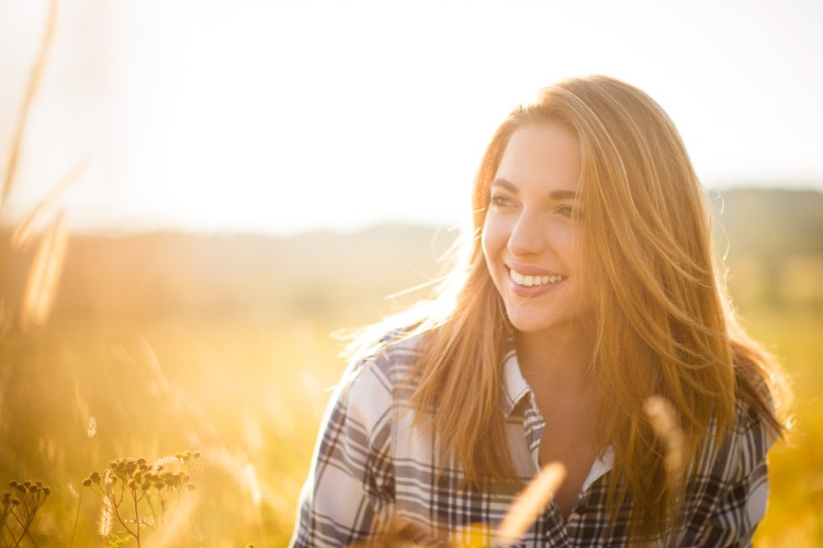 Teenage girl smiles in a yellow field after recovering from her wisdom teeth removal surgery at Summit Family Dentistry