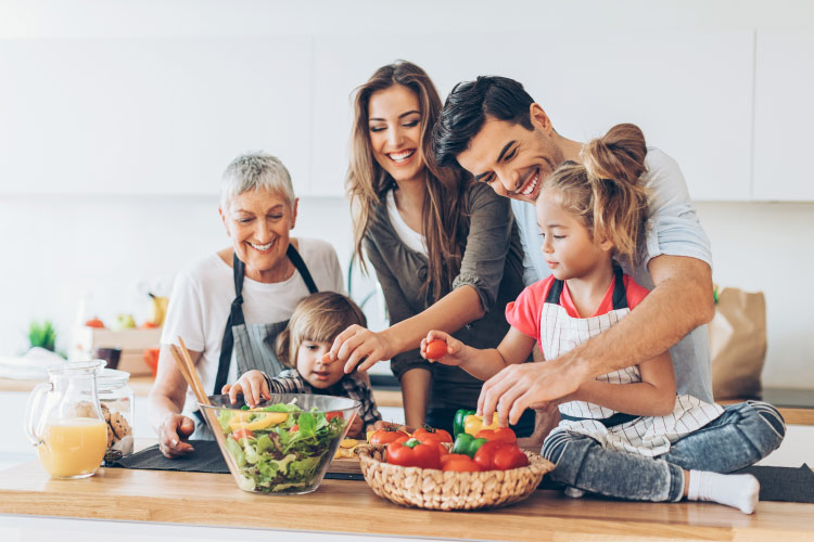 Family of a mom, dad, son, daughter, and grandmother smile as they prepare a healthy meal together in the kitchen