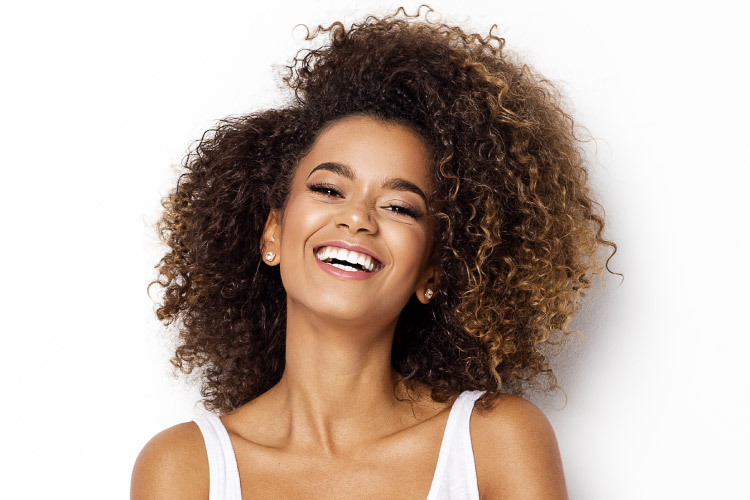 curly-haired woman smiles with dental implants while wearing a white tanktop in Littleton, CO