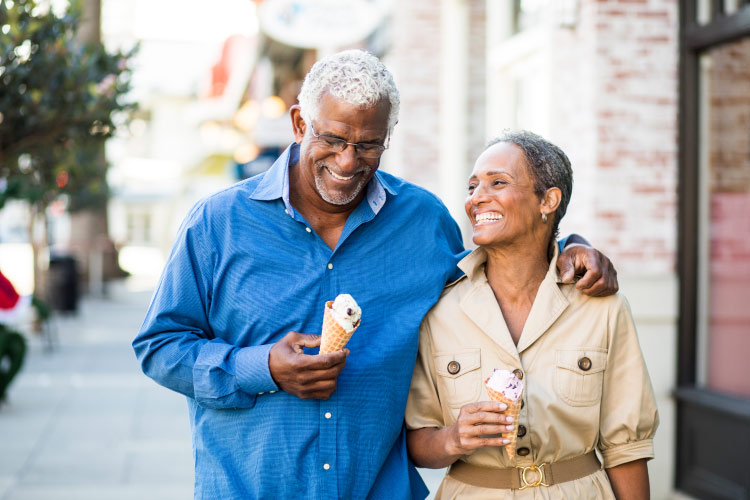 Husband and wife smile with dentures and implant-supported dentures as they walk down the sidewalk with ice cream cones