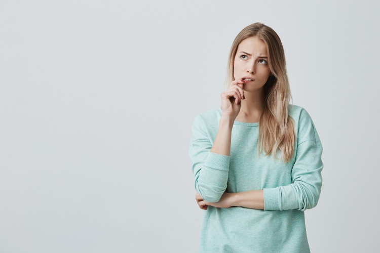 Blonde woman in a mint shirt bites her lip and worries about her receding gumline