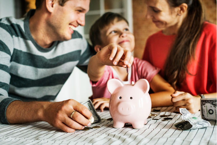 A young family consisting of father, mother and young boy are gathered around a table dropping coins in a piggy bank