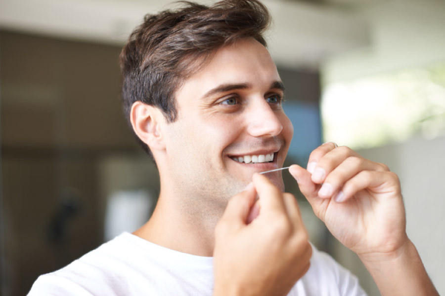 A young brunette haired man flossing his teeth.