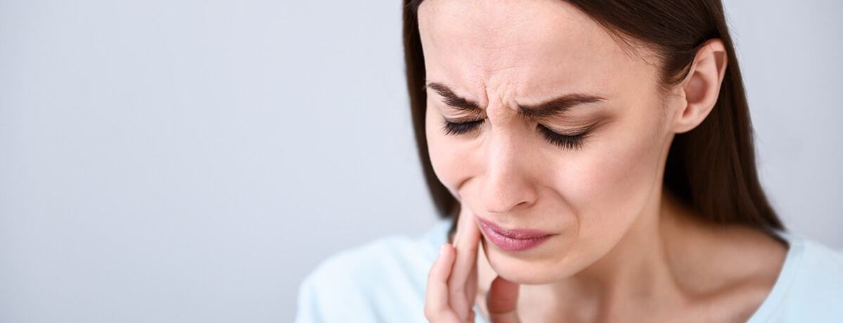 woman in a white shirt holding her jaw in pain