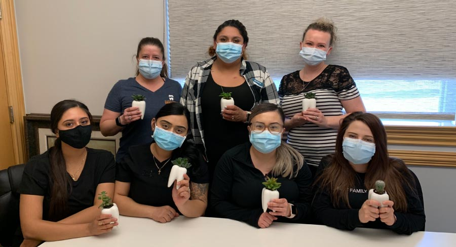 Summit Family Dentistry dental assistants gathered around a table wearing masks and holding models of a tooth.